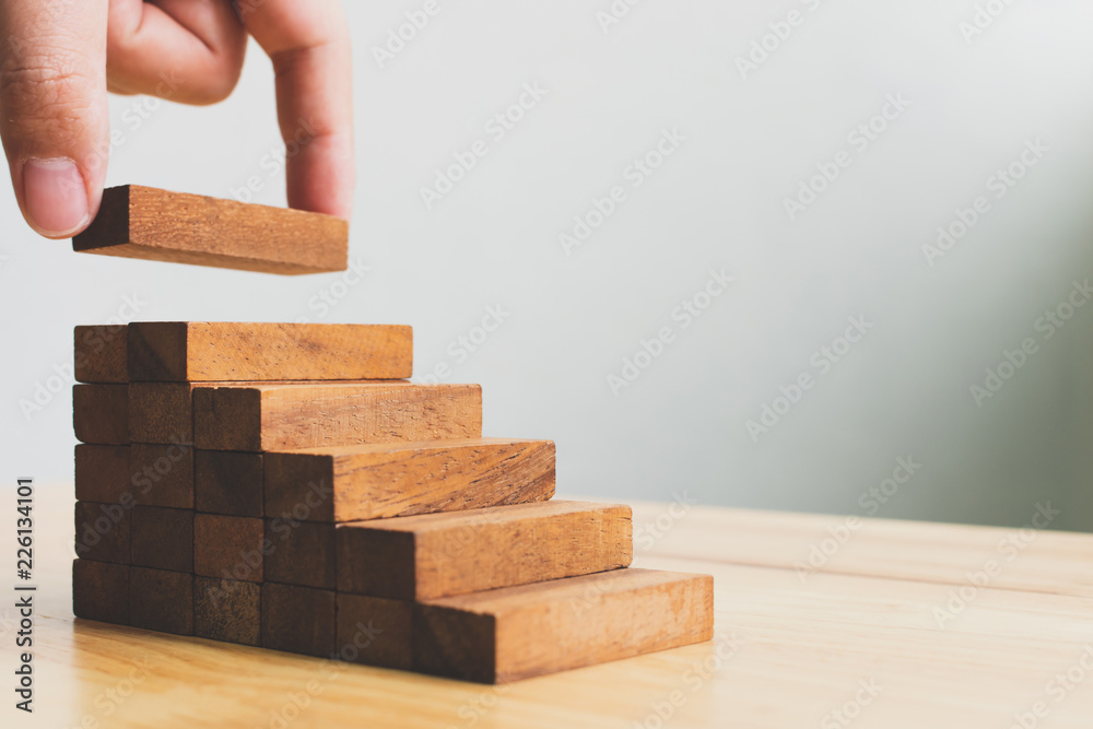 Fototapety, obrazy: Hand arranging wood block stacking as step stair. Ladder career path concept for business growth success process