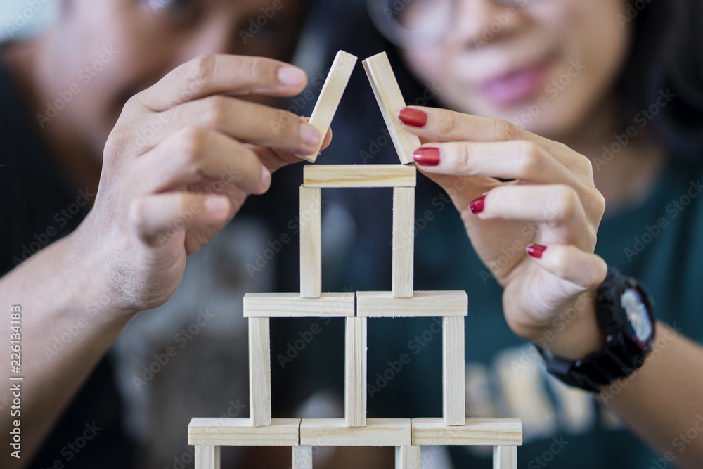 Fototapeta Young couple building a house of blocks