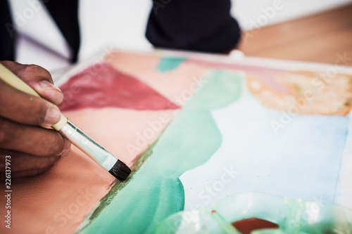 Hands asian student artist painting watercolor abstract of landscape with brush drawing on paper for creation art subject classroom at secondary education in Thailand. Creative skill, Hobbies concept