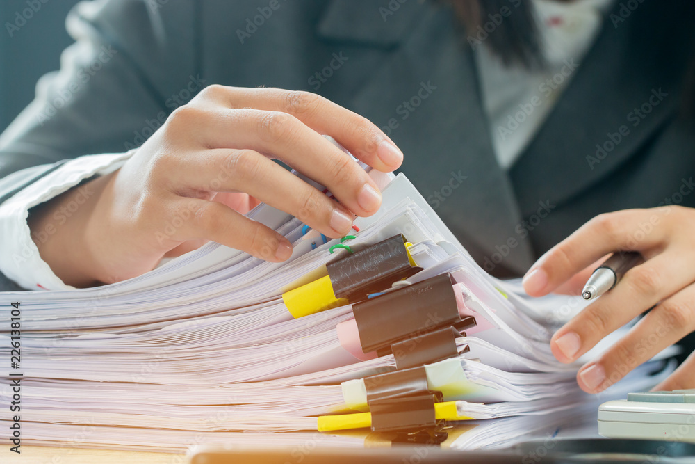 Fototapeta Accountant Business woman offices working for arranging documents unfinished stack of document papers on busy office desk for planning budget