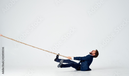 business man pulls the rope on an isolated white background Canvas Print