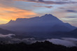 Beautiful sunrise landscape scenery with sunlight and fog and Mount Kinabalu as background in Guakon, Sabah, Malaysia