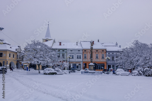 Foto op Canvas Drawn Street cafe Square during first winter snow in Czech city Valasske Mezirici