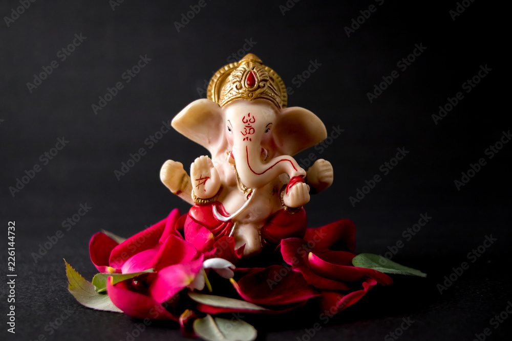 Photo  Lord Ganesha Idol with rose petals, white flowers and leaves on Black background