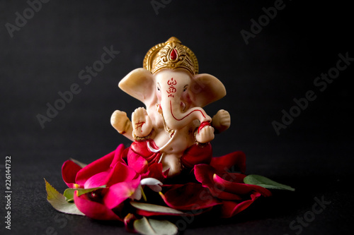 Canvas Print Lord Ganesha Idol with rose petals, white flowers and leaves on Black background