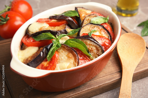 Baked eggplant with tomatoes, cheese and basil in dishware on cutting board