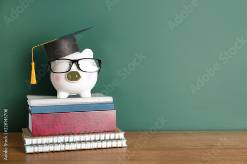 Leinwand Poster Piggy bank with graduation hat and books on table near chalkboard