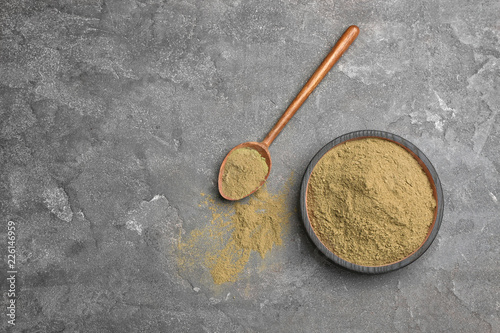 Bowl and spoon with hemp protein powder on table, top view. Space for text