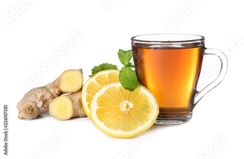 Glass cup of tea, lemon slices and ginger on white background