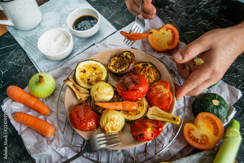 Fotografie, Obraz  Healthy and healthy food: grilled vegetables and men's hand with fork in the fra