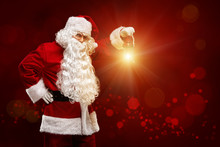 Christmas Concept. Santa Claus With A Lantern In His Hand On A Red  Background.