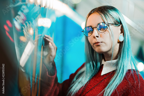 Poster Amusementspark Hipster girl with blue dyed hair and sequins as freckles. Woman in red clothing and nose piercing, transparent glasses, ears tunnels, unusual hairstyle in amusement park