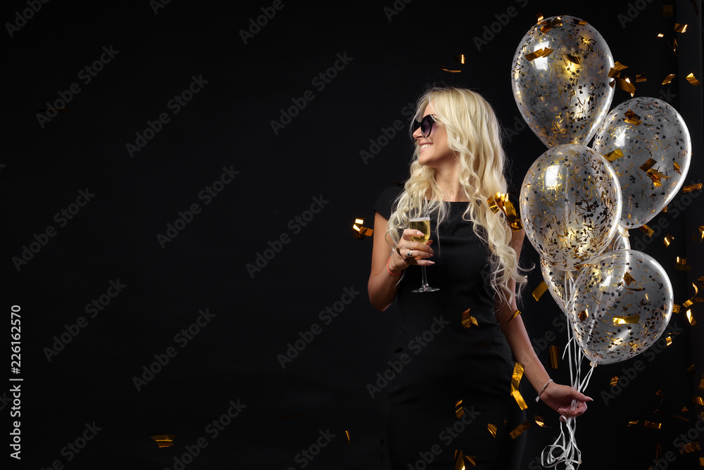 Fototapeta Brightfull expressions of happy emotions of  amazing blonde girl celebrating party on black background. Luxury black dresses, smiling, a glass of champagne, golden tinsels,  balloons, long curly hair