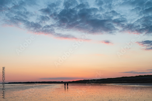 Staande foto Blauwe jeans Beautiful vibrant Summer sunset beach landscape with stunning sky and colors