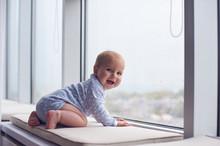 Little Baby Boy Crawlibg Near Big Window