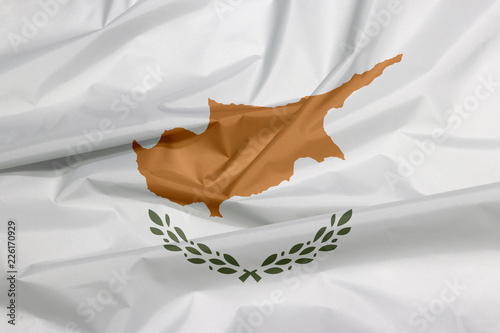 Foto op Canvas Cyprus Fabric flag of Cyprus. Crease of Cypriot flag background, an outline of the country of Cyprus above twin olive branches.