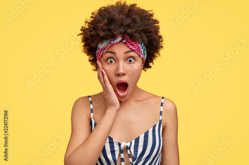 Fotografía  Shocked housewife witnessed terrible crime or accident, holds palm near widely opened mouth, has Afro hairstyle, dressed in casual striped t shirt, isolated over yellow background