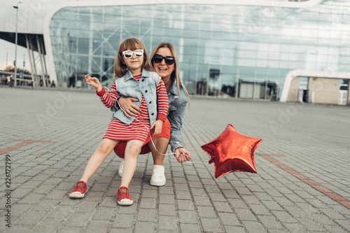 Fotografía  Beautiful Young Mother with Small Stylish Daughter Walks Through City Together