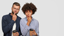 Shot Of Thoughtful Puzzled Multiethnic Young Couple Hold Chins, Try To Solve Problem, Drink Aromatic Takeaway Coffee, Stand Closely Against White Background With Copy Space For Your Advertisement.