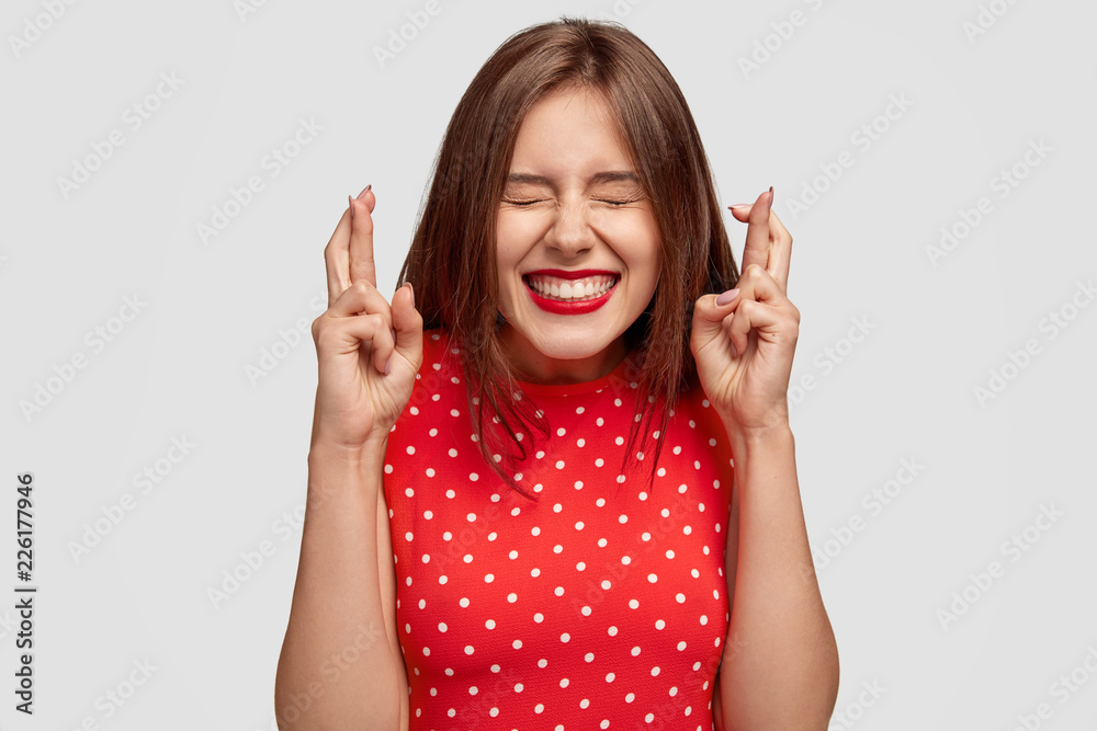 Fototapety, obrazy: Pleased attractive European woman makes wish to win, raises hands with crossed fingers, waits for lottery results, closes eyes, has red lips, dressed in fashionable dress, isolated over white wall