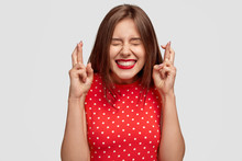 Pleased Attractive European Woman Makes Wish To Win, Raises Hands With Crossed Fingers, Waits For Lottery Results, Closes Eyes, Has Red Lips, Dressed In Fashionable Dress, Isolated Over White Wall