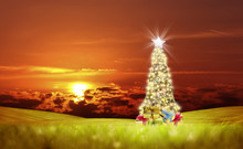 Conceptual Decorated Shiny Christmas Tree On Green Landscape Over Cloudy Red Sunset Sky