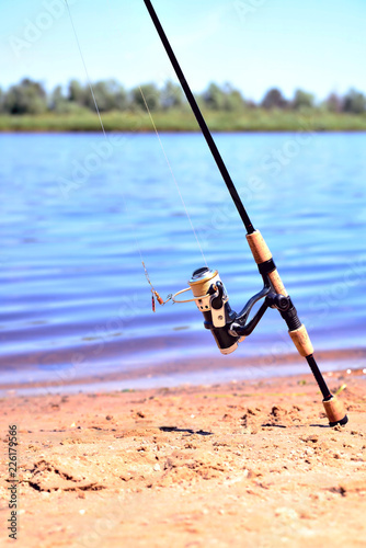 fishing rod with reel on the background of the river, blue water, sun, sand Fototapet