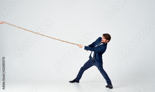 Fotografía business man in suit pulls the rope