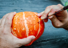 The Process Of Cutting The Halloween Pumpkins, The Process Of Making Jack-o-lantern. Men's Hands With A Knife Cut Out His Mouth