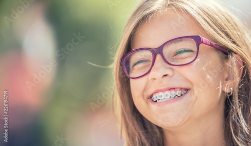 Portrait of a happy smiling teenage girl with dental braces and glasses