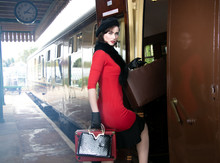 Vintage Attractive Female Wearing Red Dress And Black Beret With Suitcases On Platform Of Train Station