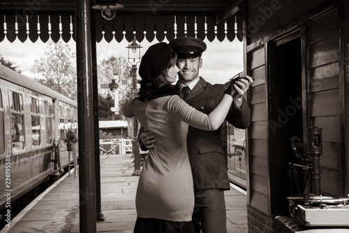 Photo Attractive couple dance on railway station platform with portable record player