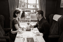 Vintage Couple Holding Hands Over Table Of Train Carriage