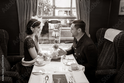 Fotografia  Vintage couple holding hands over table of train carriage