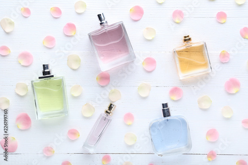 Fotografía  Perfume bottles with flower petals on wooden table