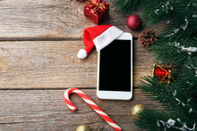 Smartphone With Red Santa Hat And Fir-tree Branch On Grey Wooden Table