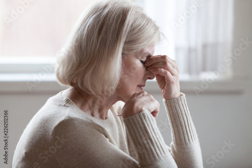 Fotografie, Obraz  Fatigued upset middle aged older woman massaging nose bridge feeling eye strain