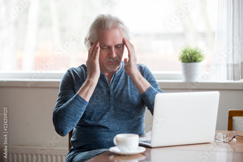 Tired fatigued middle aged senior man touching temples feeling headache migraine Fototapeta