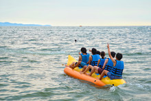 Young Boys And Girl Riding On The Banana Boat On The Sea In Pattaya, Thailand. Funny And Playful On The Summer Vacation.