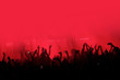 canvas print picture - Red background with a crowd of cheering people at a concert. People with their hands up