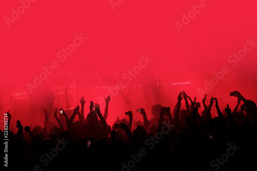 Obraz Red background with a crowd of cheering people at a concert. People with their hands up - fototapety do salonu