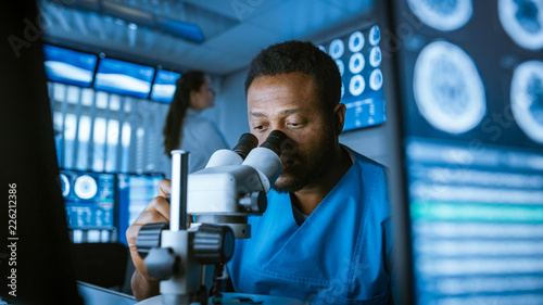 Papiers peints Akt Medical Research Scientist Looking under the Microscope in the Laboratory. Neurologist Solving Puzzles of the Mind and Brain. In the Laboratory with Multiple Screens Showing MRI / CT Brain Scan