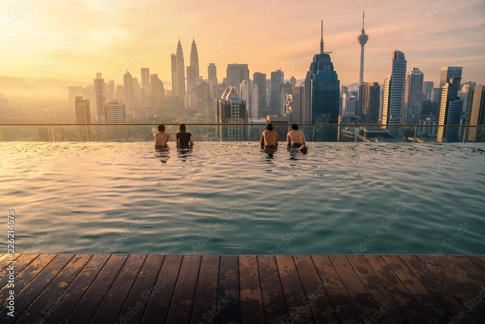 Fotografie, Obraz  Traveler looking view skyline Kuala Lumpur city in swimming pool on the roof top of hotel at sunrise in Kuala Lumpur, Malaysia