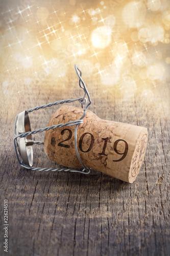 Fotografie, Obraz  Champagnerkorken auf Holz mit Lichterglanz