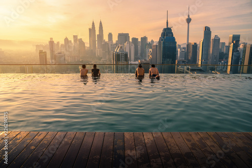 La pose en embrasure Batiment Urbain Traveler looking view skyline Kuala Lumpur city in swimming pool on the roof top of hotel at sunrise in Kuala Lumpur, Malaysia.