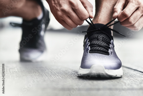 Fotografía  Close-up of sportsman tying sneakers