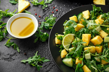 Pineapple Cucumber salad with wild green rocket, lime and olive oil. Healthy juicy food