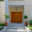 Athens Greece, contemporary house entrance wooden door and two flowerpots