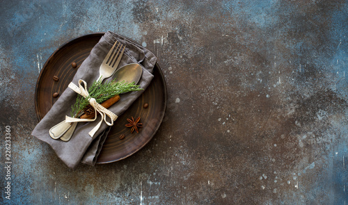 Chrismas table place setting. Tableware with evergreen twigs, cone and spice