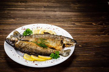Fototapeta Fish dish - fried fish fillet on wooden table